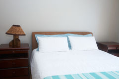 Beautiful bedroom interior. With white sheets and bedside tables Royalty Free Stock Photography
