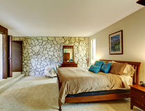 Beautiful bedroom interior with rock wall Royalty Free Stock Photography