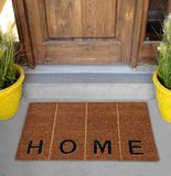 Beautiful Beige and black zute / coir Outdoor Door mat with `H O M E` text and vertical lines outside home with yellow flower pots