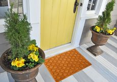 Beautiful Beige color zig-zag patterned Welcome zute doormat with border outside home with yellow flowers and leaves. Beautiful Beige color zig-zag patterned stock photo