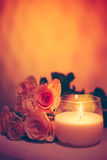 Beautiful beige roses and burning candle Royalty Free Stock Images