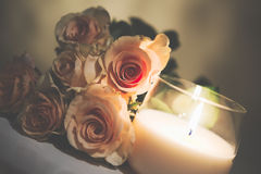 Beautiful beige roses and burning candle Royalty Free Stock Photography
