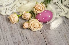 Beautiful beige roses with easter egg, feathers and knitted napkin on a textured wooden table. Great retro design for any purposes. Vintage rose. Retro easter royalty free stock photos
