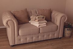 Beautiful beige textile sofa chesterfild in the interiors royalty free stock images