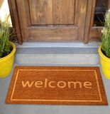 Beautiful beige Welcome zute doormat with Border outside home with yellow flowers and leaves. Beautiful beige Welcome zute doormat with Border outside home with royalty free stock image