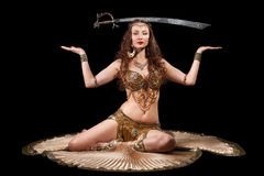 Beautiful belly dancer balancing sword Royalty Free Stock Image
