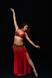 Beautiful belly dancer performing exotic dance. Dark background Royalty Free Stock Photo