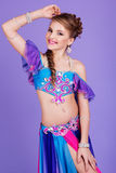 Beautiful belly dancer wearing a purple costume Royalty Free Stock Photo
