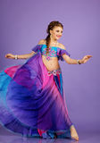 Beautiful belly dancer wearing a purple costume Royalty Free Stock Images