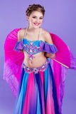 Beautiful belly dancer wearing a purple costume Royalty Free Stock Photography