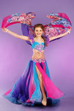 Beautiful belly dancer wearing a purple costume Stock Photos