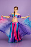 Beautiful belly dancer wearing a purple costume Stock Photo