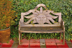 Beautiful bench with woodcarving of the sun Stock Photos