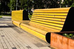 Beautiful benches with an unusual flowerbed near the footpath of royalty free stock images