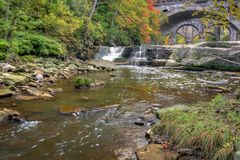 Beautiful Berea Falls In Autumn. Berea Falls Ohio with fall colors. This cascading waterfall looks it`s best with autumn colors in the trees. The stone arch royalty free stock images