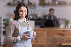 Beautiful bespectacled woman smiling and holding cup. Tea time. Happy pretty woman smiling and holding cup of tea while standing in a cafe Stock Photography