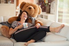 Beautiful best age woman lying on the couch relaxing, with a huge teddy bear royalty free stock photos