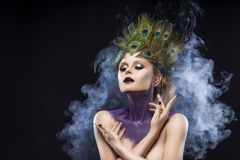 Beautiful big breast girl wearing peacock feathers in her hair a. Nd artistic violet shiny body art on her neck, vanguard makeup artistically crossed her hands Royalty Free Stock Photo