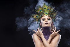 Beautiful big breast girl wearing peacock feathers in her hair a. Nd artistic violet shiny body art on her neck, vanguard makeup artistically crossed her hands royalty free stock image