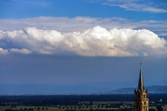 Beautiful big cloud over the belltower of old church Royalty Free Stock Photo
