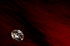 Beautiful big diamond jewelry on dark red background. Fine natural precious stone.Brillant shine.  Royalty Free Stock Images