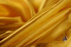 Beautiful big diamond jewelry on golden satin cloth background. Fine natural precious stone Stock Images