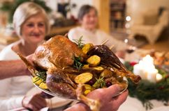 Family celebrating Christmas. Roasted turkey on tray. Beautiful big family sitting at the table celebrating Christmas together at home. Close up of roasted Stock Image