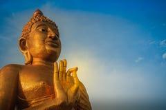 Beautiful big golden Buddha statue on the hilltop at Wat Khao Ba. Ndai It, Phetchaburi, Thailand. Huge golden Buddha statue with blue sky background Royalty Free Stock Image