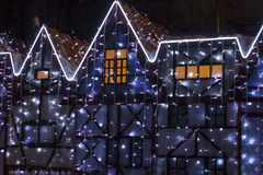 Beautiful big house decorated with Christmas lights. Large Windows with Christmas tree. stock photography
