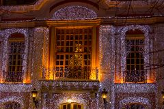 Beautiful big house decorated with Christmas lights. Large Windows with Christmas tree. New year old manor stock photo