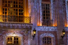 Beautiful big house decorated with Christmas lights. Large Windows with Christmas tree. New year old manor stock photography