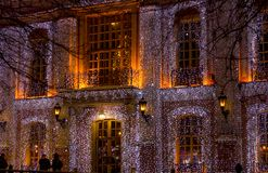 Beautiful big house decorated with Christmas lights. Large Windows with Christmas tree. New year old manor stock image