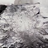 Beautiful big piece of ice with abstract cracks. Icicle bellow waterfall, stony and messy stream bank Royalty Free Stock Photos
