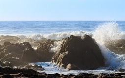 Beautiful big rock on oceanic beach with big waves and water splashes Stock Image