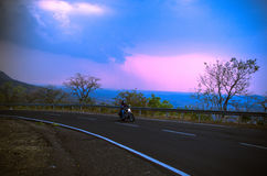 Beautiful Bike Ride... A rider enjoying a bike ride at picturesque location of malshej ghat in western ghats of India Stock Photo