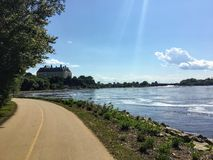A beautiful bike and walking path along the ottawa river on a sunny summer day with blue sky.  The Supreme Court of Canada is back stock images