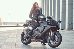 A beautiful biker girl sitting on her superbike outside a building. A beautiful biker girl wearing black leather jacket sitting on her superbike outside a stock photography