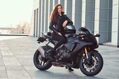 A beautiful biker girl sitting on her superbike outside a building. A beautiful biker girl wearing black leather jacket sitting on her superbike outside a royalty free stock images