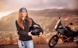 Beautiful biker girl. Standing on the road with helmet in hands near motorbike, traveling in overcast weather along high mountains, active lifestyle concept Royalty Free Stock Photos
