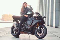 A beautiful biker girl leaning on her superbike outside a building. A beautiful biker girl wearing black leather jacket leaning on her superbike outside a royalty free stock photo