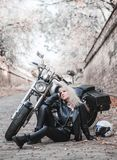 Beautiful biker woman outdoor with motorcycle. Beautiful biker woman posing outdoor with motorcycle stock images