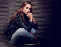 Beautiful biker woman thinking in black fashion jacket and jeans. On street wall background. Dark portrait with shadows Stock Image