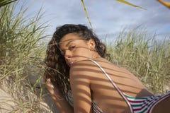 Beautiful bikini girl lying on a beach and looking Stock Photography