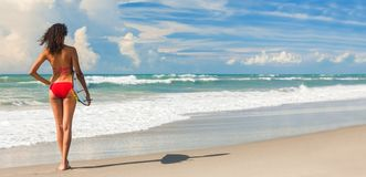 Beautiful Bikini Woman Girl Surfer & Surfboard Beach Panorama. Panoramic banner image rear view of beautiful young woman surfer girl in red bikini with surfboard stock images