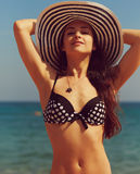 Beautiful bikini woman in hat on blue sea Stock Photos