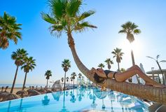 Woman lying on pool bent palm tree trunk. Beautiful bikini woman lying on bent palm tree trunk at resort pool on the beach Stock Photography