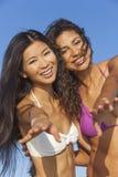 Beautiful Bikini Women Girls Laughing At Beach. Two beautiful young women in bikinis having fun laughing and dancing partying together on a sunny beach with blue royalty free stock photo