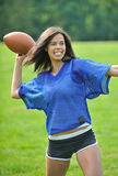 Beautiful biracial female football player. Stunning young biracial (African American and Caucasian) woman football (American) player smiling in blue mesh jersey royalty free stock image