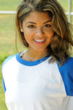 Beautiful biracial female softball player. Portrait of smiling, beautiful young woman in blue and white baseball shirt stock images