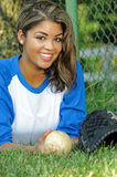 Beautiful biracial female softball player. Portrait of smiling, beautiful young woman in blue and white baseball shirt laying on ground with ball and glove royalty free stock photos